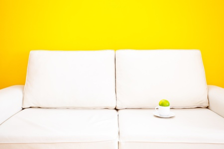 white sofa and cup with tangerine against a yellow wall in the apartment photo