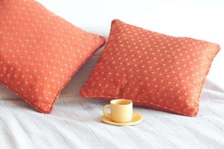 bed with two pillows, a cup of tea on the blanket photo