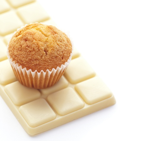 bar of white chocolate and muffin isolated on white photo