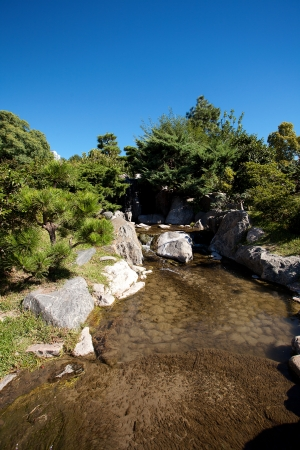 coniferous trees, rocks and a waterfall on a background of blue sky photo
