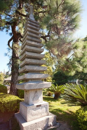 stone pagoda on the background of green trees photo