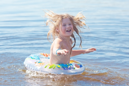 beautiful little girl splashes in the water photo