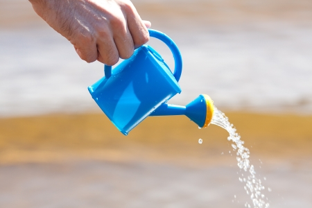 hand of a man with a watering can on a background of water photo