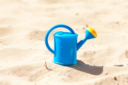 watering can on a background of sand photo