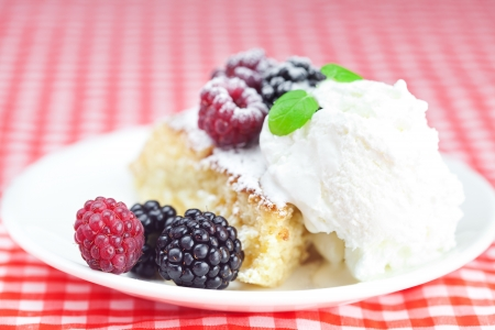 cake with icing,icecream, raspberry, blackberry and mint on a plate on plaid fabric photo
