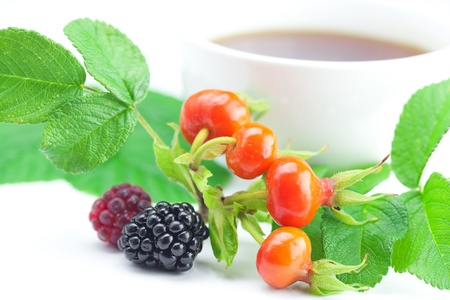 cup of tea, blackberry,raspberry and rosehip berries with leaves on white background photo