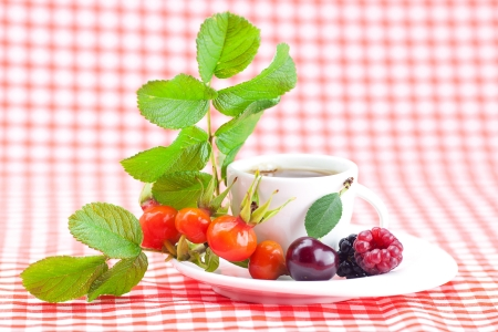 cup of tea, blackberry,raspberry and rosehip berries with leaves on plaid fabric photo
