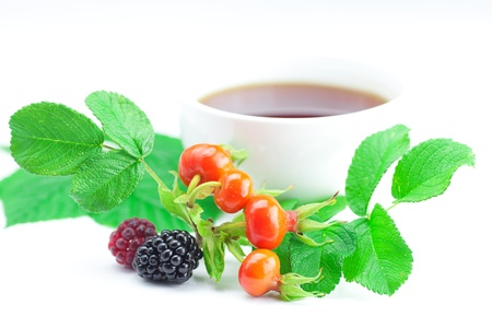 cup of tea, blackberry,raspberry and rosehip berries with leaves photo
