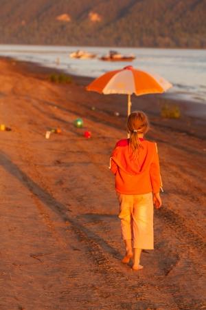 little girl running along the beach in the sunshine photo