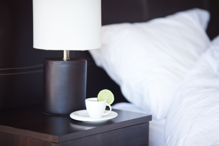 hotel stay: bed with a pillow, a cup of tea on the bedside table and lamp Stock Photo