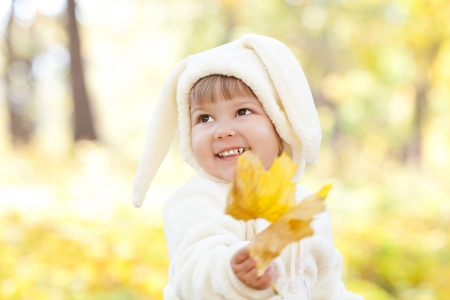 beautiful little girl in costume bunny in the autumn forest photo