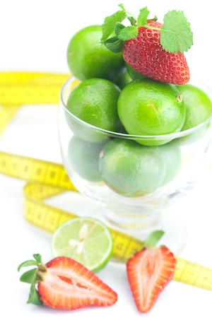 lime in a glass cup, measuring tape, strawberry and mint isolated on white Stock Photo - 17601134