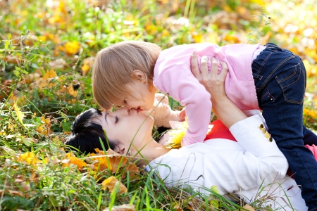 beautiful young mother and her daughter lying on the autumn leaves Stock Photo