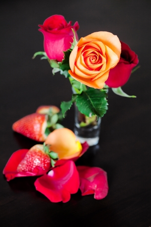 bouquet of colorful roses in a vase and strawberry on a wooden table photo