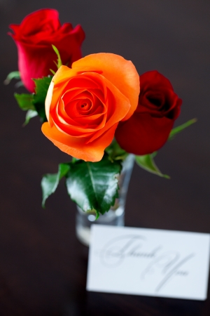 bouquet of colorful roses in a vase and card with the words thank you on a wooden table photo