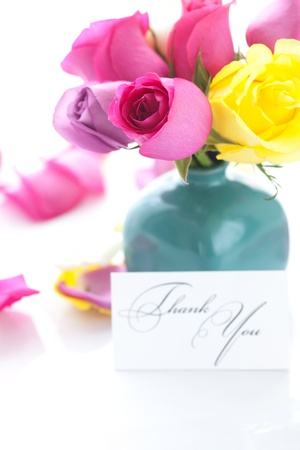 bouquet of colorful roses in vase,petals and card with the words thank you photo