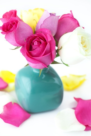 bouquet of colorful roses in vase and petals  photo
