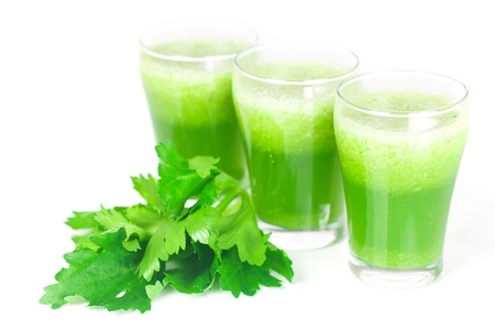 celery and three glasses with celery juice isolated on white photo