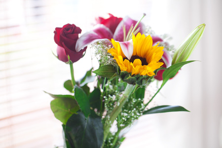 beautiful bouquet of sunflowers, lily and roses in a vase photo