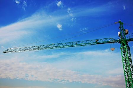 tower crane above the city on a background of blue sky photo