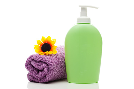 cosmetic containers,towel and sunflower isolated on white photo