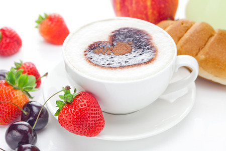 cappuccino in a cup in the shape of hearts,cherry,croissant  and strawberries isolated on white photo