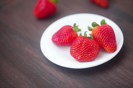 red juicy strawberry in a plate on a wooden surface