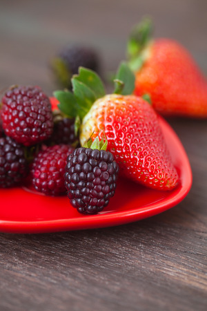 red juicy strawberry in red plate on a wooden surface Standard-Bild