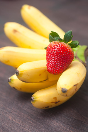bunch of bananas anf strawberry on a wooden surface