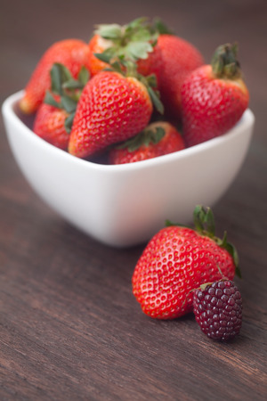 red juicy strawberry  in a bowl on a wooden surface Standard-Bild