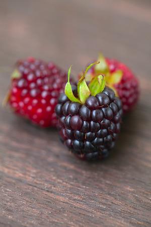 three juicy blackberries on a wooden surface