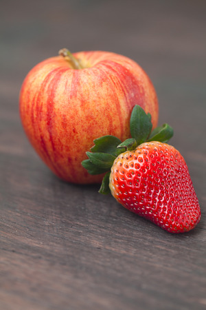 juicy apple and strawberry on a wooden surface