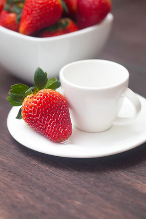 red juicy strawberry in a bowl and cup on a wooden surface