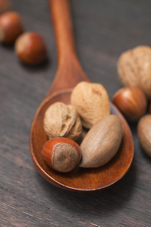 wooden spoon with nuts on a wooden surface Standard-Bild