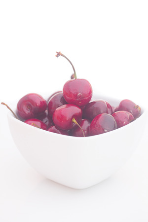 Cherries  in white bowl isolated on white Standard-Bild