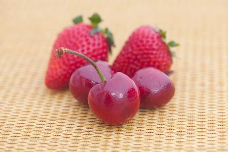 strawberries and cherries on wicker mat Standard-Bild