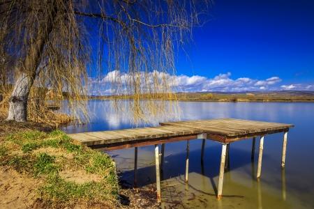 cloud drift: Fishing pier at the lake,Romania Stock Photo