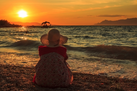 bad feeling: Lonely sad woman in the sunset on the beach Stock Photo