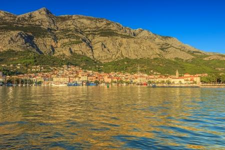 Medieval cityscape harbour and Biokovo mountains in Makarska, Croatia photo