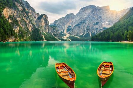 Barche su un lago di montagna e il sole delle Alpi dolomitiche, Sudtirol, Italia, Europa Archivio Fotografico