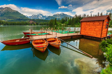 Stunning mountain lake with colorful wooden boats in the National Park High Tatras,Strbske Pleso,Slovakia,Europe