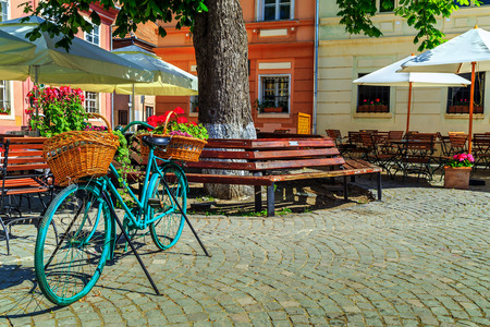 romantic places: Stone paved old street with cafe bar and old bicycle in Sighisoara fortress,Transylvania,Romania,Europe Stock Photo