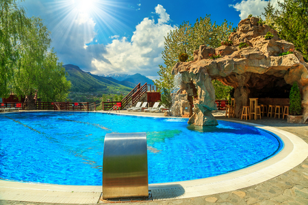 deep blue: Stunning swimming pool of luxury hotel with cave bar and magical landscape on background