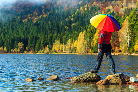 beach landscape: Hiker woman with colorful umbrellas,St Ana Lake,Carpathians,Transylvania,Romania,Europe