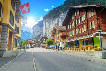 Hoofdstraat van Lauterbrunnen met winkels, hotels, terrassen, Zwitserse vlaggen en prachtige Staubbach waterval op de achtergrond, Berner Oberland, Zwitserland, Europa