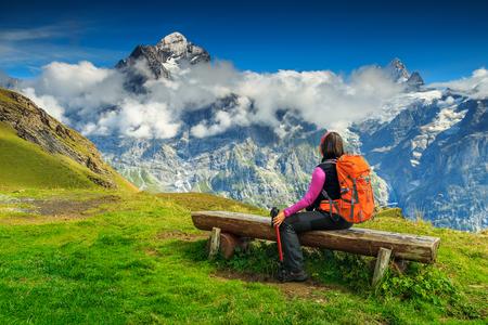 Jonge vrouw toeristische ontspannen op de bank, te genieten van het panorama met Wetterhorn bergen, gletsjers en groene velden in de buurt van Grindelwald, Berner Oberland, Zwitserland, Europa