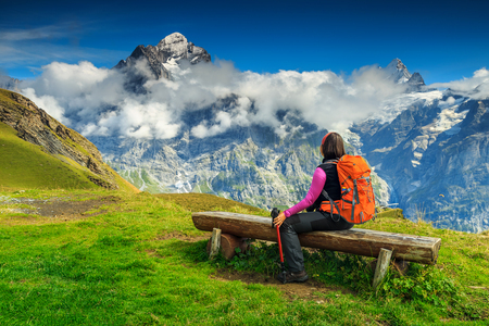 Young woman tourist relaxing on the bench,enjoying the panorama with Wetterhorn mountains,glaciers and green fields near Grindelwald,Bernese Oberland,Switzerland,Europe