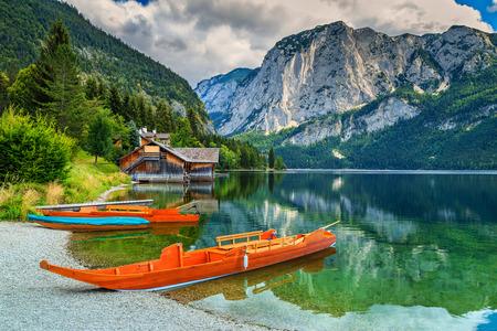 landschap: Houten aanlegsteiger met traditionele boten en hoge rotsachtige bergen op de achtergrond, Altaussee, Salzkammergut, Oostenrijk, Europa