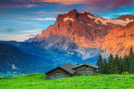 snowy mountains: Beautiful alpine landscape,old Swiss traditional wooden hut and magical sunset with Wetterhorn peak in background,Grindelwald,Bernese Oberland,Switzerland,Europe