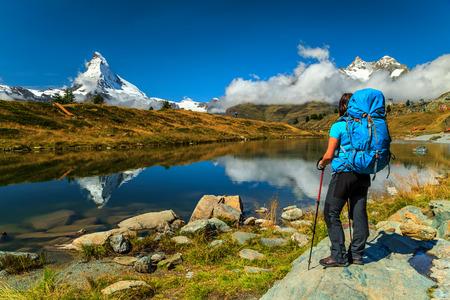 mochila de viaje: Mujer del caminante con mochila mirando a ver en la región de Valais, lago Leisee, Suiza, Europa Foto de archivo